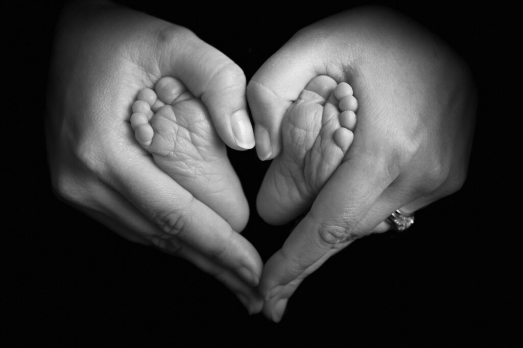 Mothers Day hand holding baby's feet.